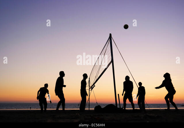 Silhouettes of a group of young people playing beach volleyball on the beach in Brittany, France - Stock Image