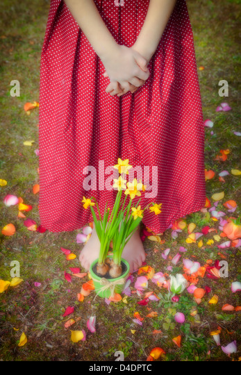 a girl is standing in front of daffodils - Stock-Bilder