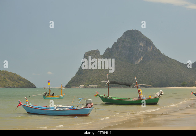 beached fishing boats in Prachuap Kiri Khan Harbour, Gulf of Thailand, Thailand - Stock Image