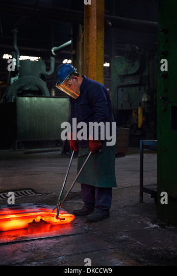 Fully forged and clipped flight bar (mining component) is lined up to cool down for final stage of finishing process - Stock Image