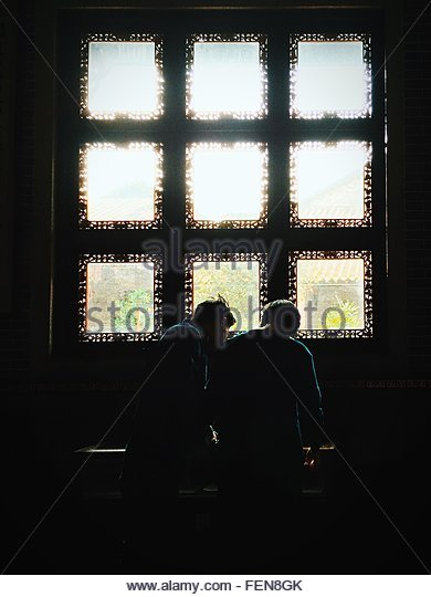 Rear View Of Two People Standing By Window - Stock Image