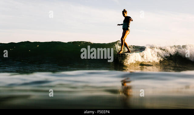 Woman surfing at sunset, Malibu, California, USA - Stock Image