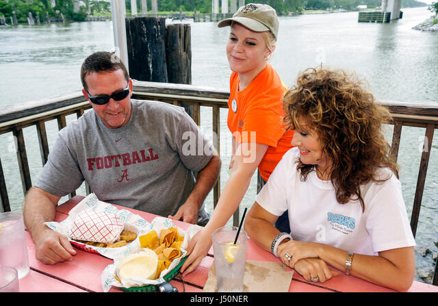 Gulf Shores Alabama Lulu's restaurant dining seafood Intracoastal Waterway waitress serving man woman couple - Stock Image