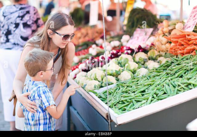 mother and son buying green peas at a vegetable market - Stock Image