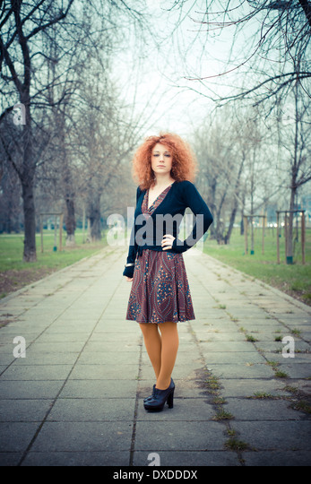 young beautiful red curly hair woman at the park - Stock Image