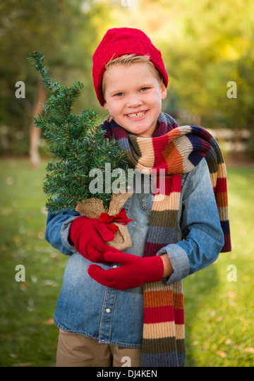 Handsome Young Boy Wearing Holiday Clothing Holding Small Christmas Tree Outside. - Stock-Bilder