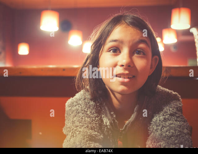 Girl sits at tab;e in restaurant - Stock Image