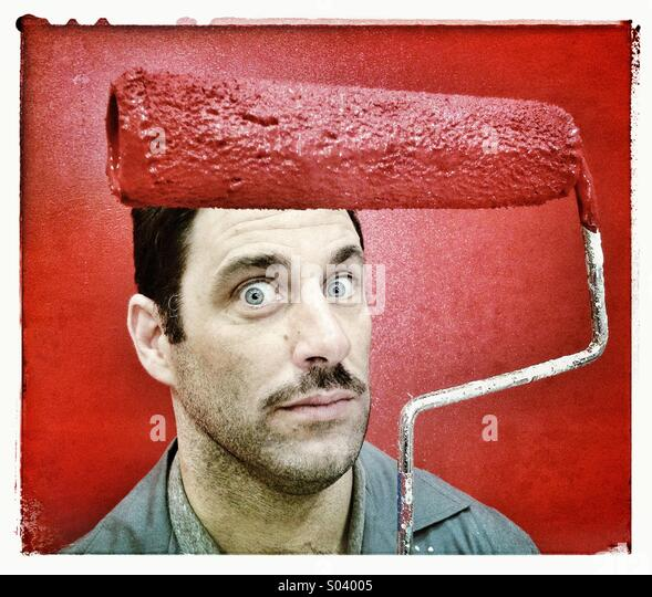Painter with red paint roller - Stock Image