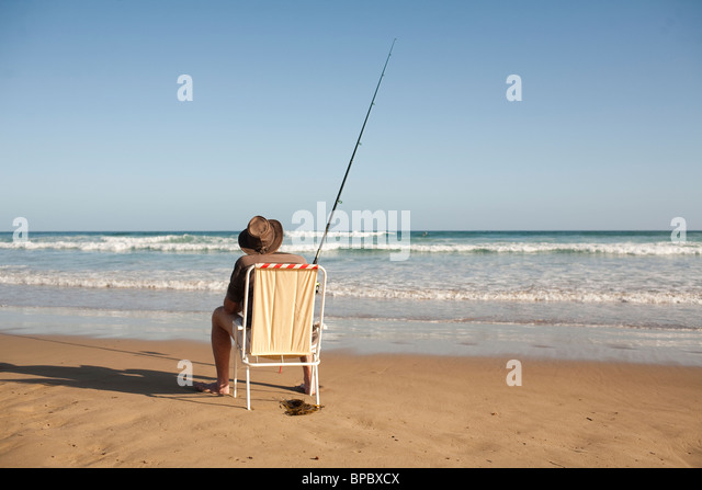Fisherman sitting in a beach chair surf casting in the ocean - Stock Image