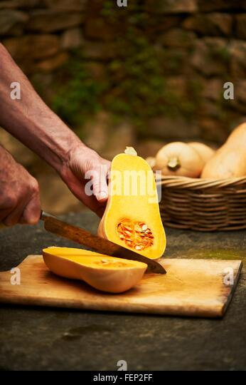 Senior mans hands chopping butternut squash with knife on cutting board - Stock Image