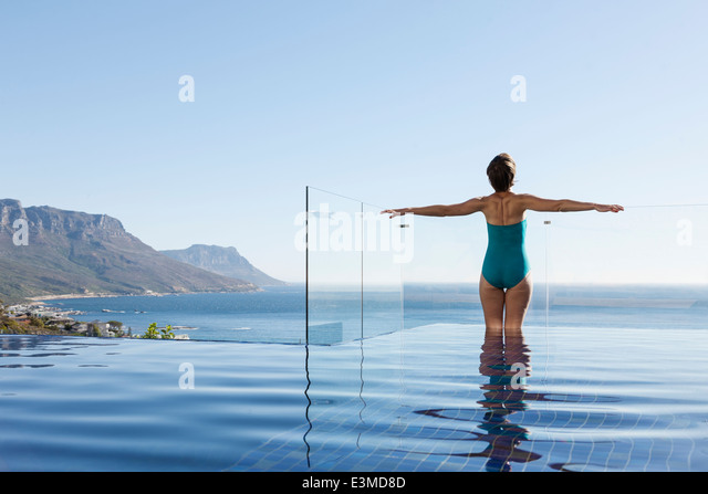 Woman basking in infinity pool overlooking ocean - Stock Image