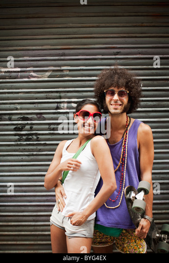 Portrait of young couple embracing by garage door - Stock Image