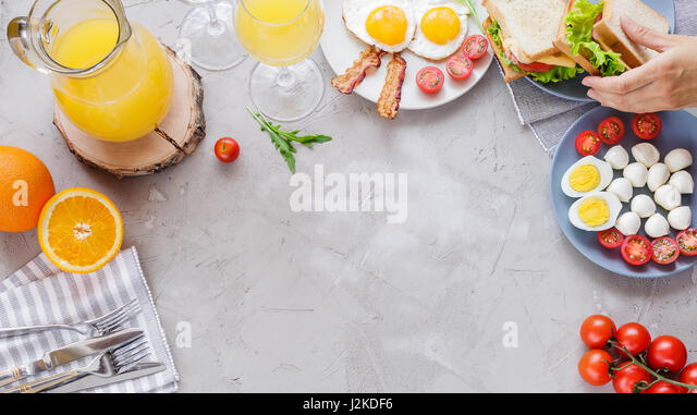 Breakfast table with fried eggs, bacon, cherry tomatoes, sanwiches, orange juice - Stock Image