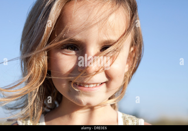 Young girl with hair blowing in her face - Stock-Bilder