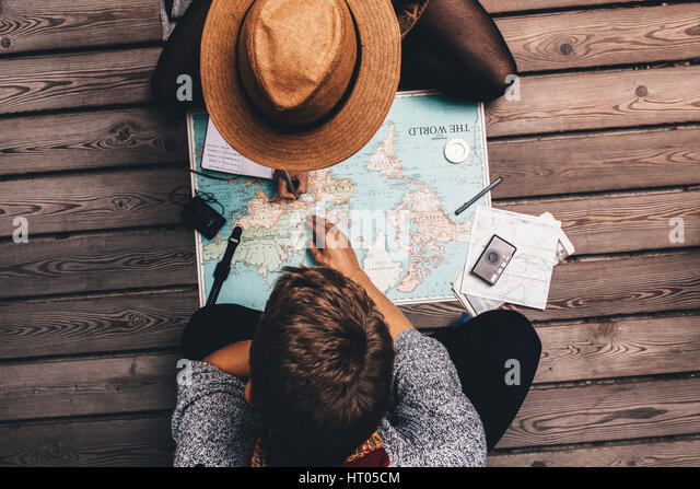 Man and woman making vacation plans using the world map. Couple sitting by the map and exploring it. - Stock Image
