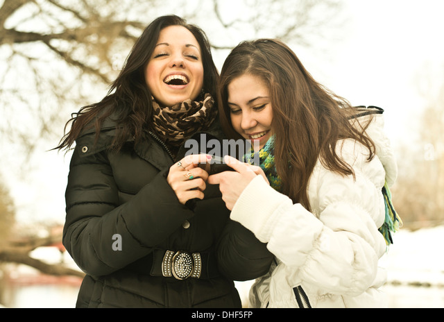 Two young women laughing at mobile phone in park in winter - Stock Image