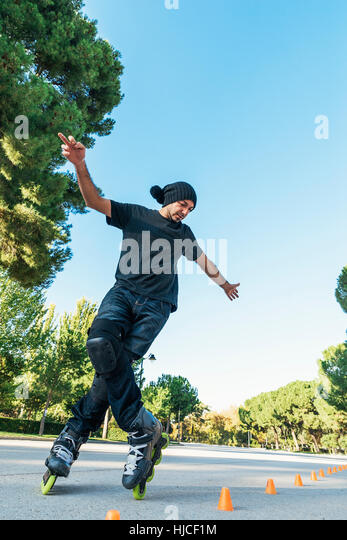Urban young man on roller skates on the road at summer time. Roller Concept - Stock Image