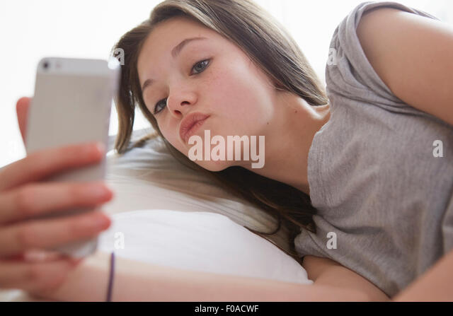 Girl lying on bed peering at smartphone text message - Stock Image