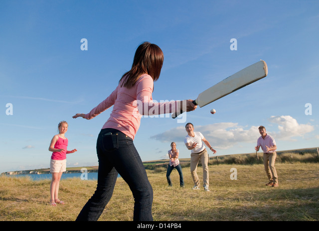 Family playing cricket together outdoors - Stock Image