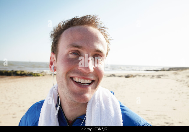 Happy man on beach after exercise - Stock Image