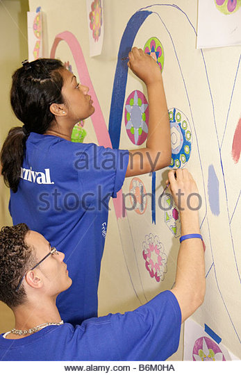 Miami Florida Overtown Hands on Miami Day volunteers community event Citrus Grove Middle School painting mural hall - Stock Image
