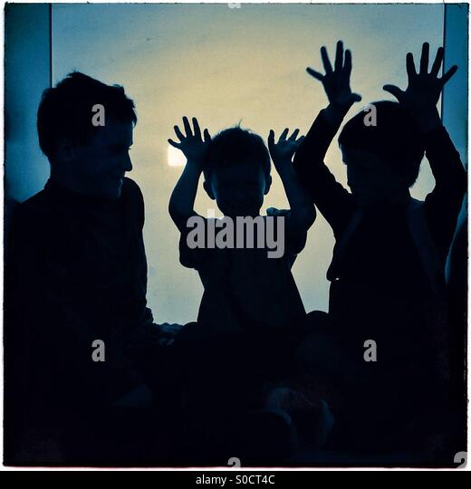 Three children silhouettes playing with hands up - Stock Image