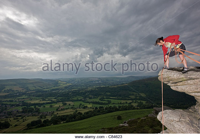 Rock climber pulling rope over cliff - Stock Image