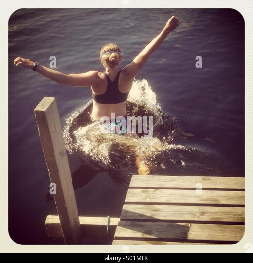 A woman jumping off a pier into a lake - Stock Image
