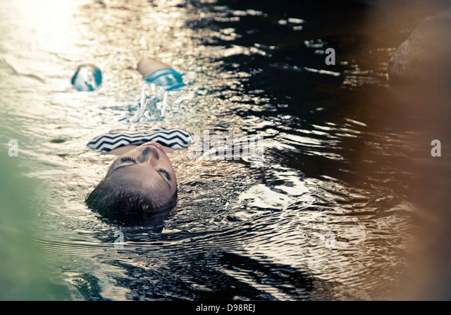 Woman floating in water during sunset - Stock Image