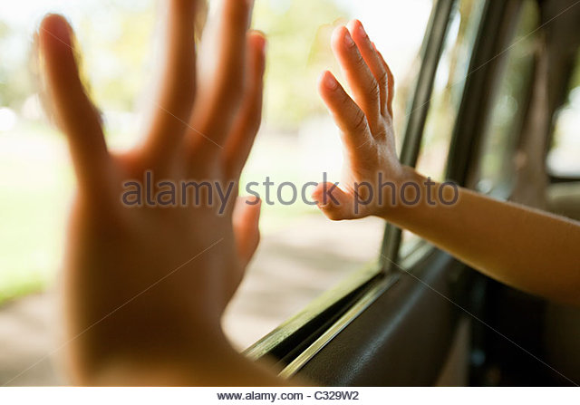 Child's hands touching car window - Stock Image