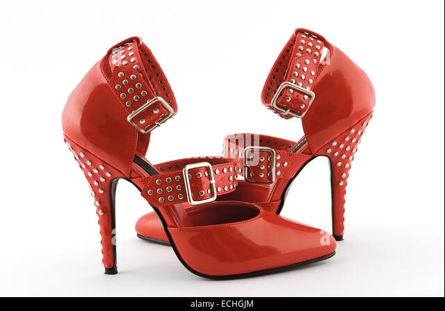Sexy red stiletto high heels with studs and buckles, isolated on a white background. - Stock Image