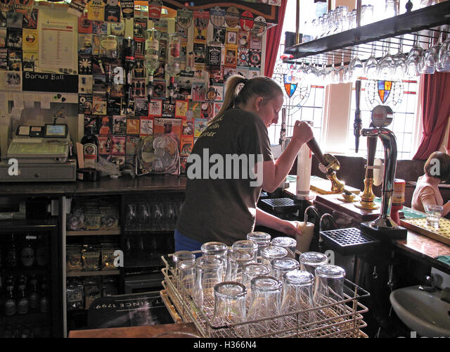 Pulling a handpull pint in a Yorkshire pub,with empty glasses, England, UK - Stock Image