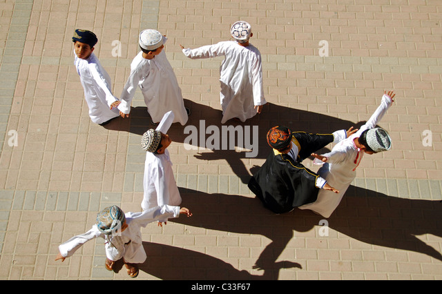 Oman, Muscat, top view of school boys standing with arms out and dancing on the ground on a sunny day - Stock-Bilder