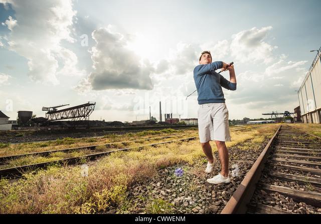 Man playing golf on train tracks - Stock Image