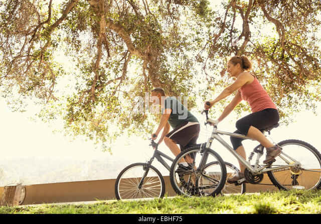Mature couple cycling in park - Stock Image