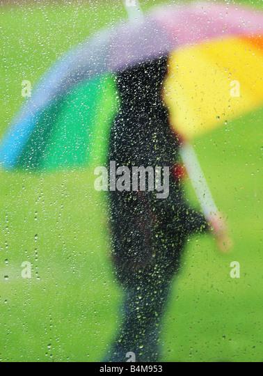 person stood with umbrella in the rain - Stock Image