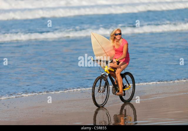 A surfer riding a mountain bike to the ocean. - Stock-Bilder