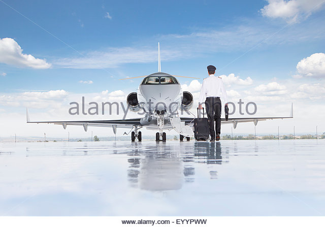 Pilot walking towards private jet - Stock-Bilder
