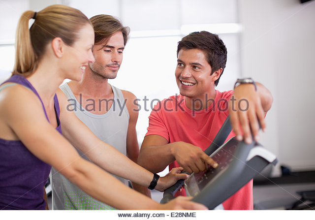 Men helping woman with treadmill in gymnasium - Stock Image