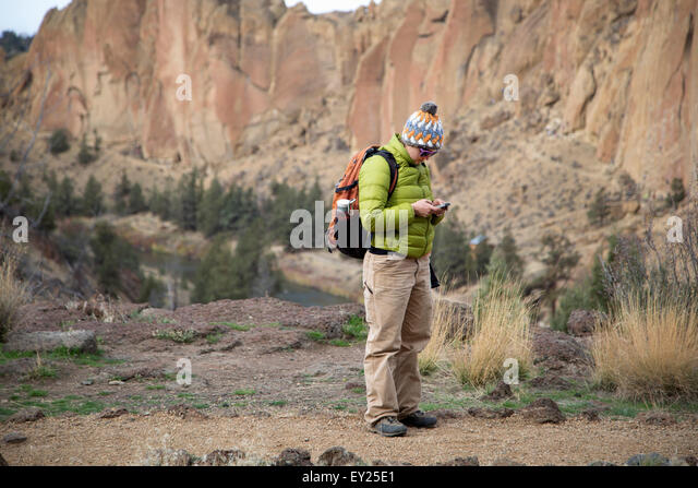 Hiker checking phone, Smith Rock State Park, Oregon, US - Stock Image
