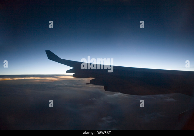 Port wing of a Boeing 747-400 of Cathay Pacific airliner, seen from passenger window silhouetted against glow of - Stock Image