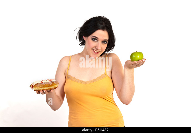 A young woman tries to decide beween a healthy apple and an unhealthy doughnut. - Stock Image