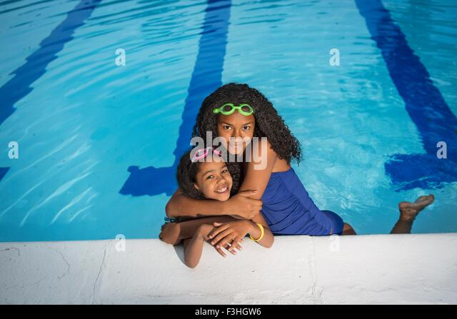 Girl in swimming pool with arms around little sister, looking at camera smiling - Stock Image