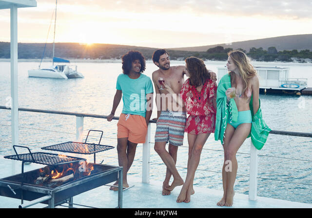 Young adult friends hanging out and drinking on summer houseboat - Stock-Bilder