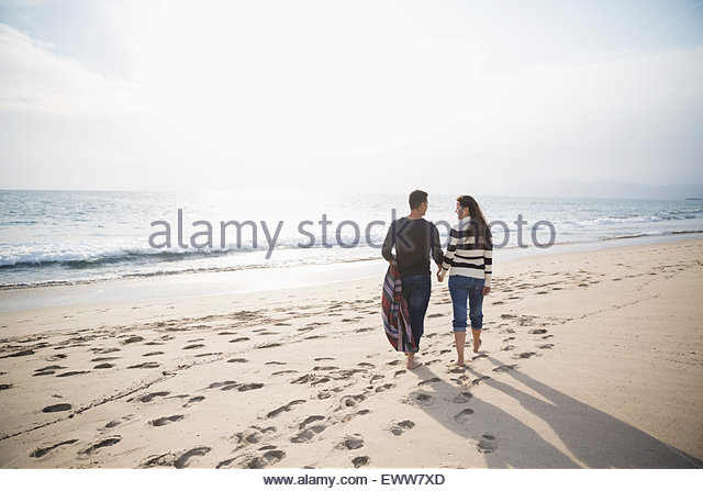 Couple walking on sunny beach - Stock Image