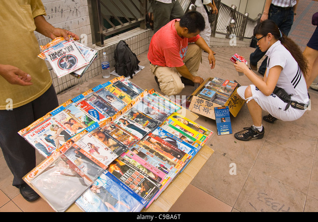 GUANGZHOU, GUANGDONG PROVINCE, CHINA - Street vendor selling pirate DVDs of current hit movies and television shows, - Stock Image
