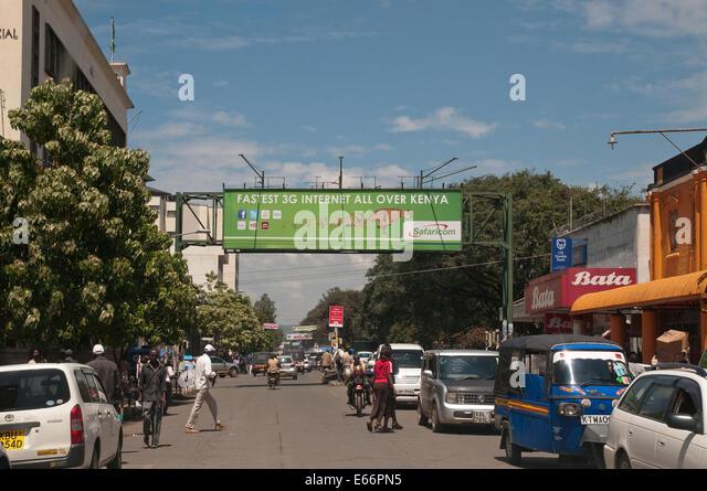 People and traffic on Kenyatta Avenue Nakuru Kenya East Africa with advertising hoarding for 3g Network - Stock Image