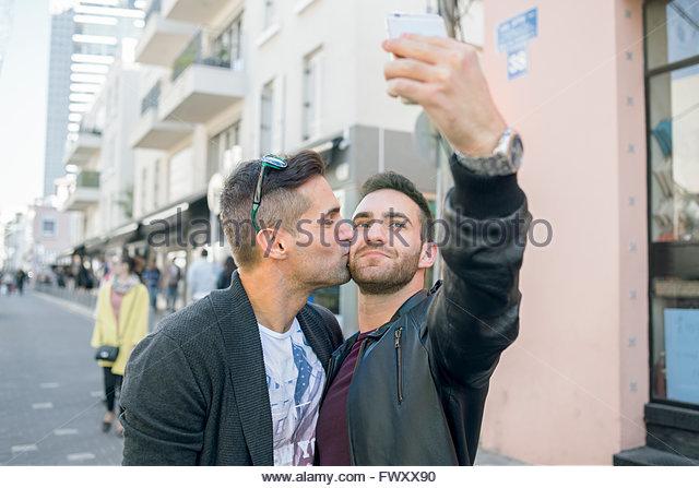 Israel, Tel Aviv, Homosexual couple taking selfie in street - Stock-Bilder