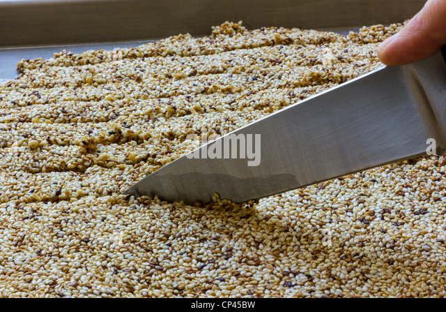 Making Pasteli a Greek honey and sesame candy - Stock Image