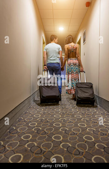 Young couple standing at hotel corridor upon arrival, looking for room, holding suitcases. - Stock Image